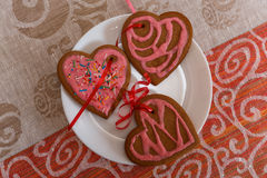 Chocolate gingerbread cookies heart shaped with red and pink icing on white plate Stock Images