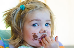 Blond baby girl with chocolate on her face Royalty Free Stock Images