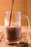 Chocolate in glass pouring from top on wood table Stock Photography