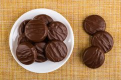 Chocolate cookies in plate and cookies on mat. Top view stock images