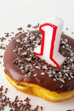 Chocolate Glazed Donut with a Number One Candle Royalty Free Stock Image