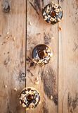 Chocolate glazed donuts with hazelnuts on wooden background, top view royalty free stock photos