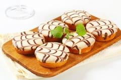 Chocolate-glazed mini cakes Stock Images