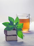 Chocolate glazed soufflé candies with cup of tea and mint leaf. Upon wooden table Royalty Free Stock Image