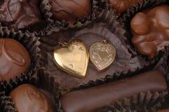 Chocolate and Gold Hearts. Two gold hearts among handmade chocolates. Focus = the gold hearts. 12MP camera, macro Royalty Free Stock Photos