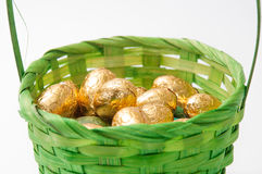 Chocolate golden easter egg in green basket Stock Image