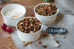 Chocolate granola in two cups with goji and milk Royalty Free Stock Photography