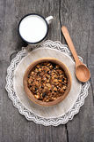 Chocolate granola in wooden bowl and milk Stock Photo