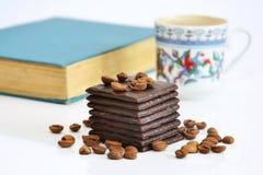 Chocolate, granos de café, café y libro fotos de archivo