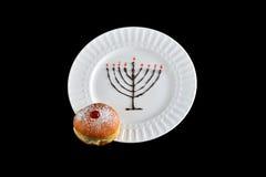 Chocolate hanukkiah with jam filled sufganiyah on a white plate. Hanukkah symbols presented using sweet food. Chocolate and jam stock image