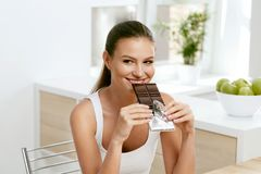 Chocolate. Happy Woman Biting Chocolate Bar. Portrait Of Beautiful Young Smiling Woman Enjoying Dark Chocolate Indoors. Diet And Nutrition Concept. High royalty free stock images