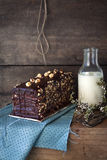 Chocolate and hazelnut cake. Dark rustic setting with a homemade chocolate and hazelnut cake, bottle of milk and blue napkin royalty free stock images