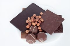 Chocolate, hazelnut and chocolate marshmallow are lying on a white plate. Nutritious food. Stock Photos