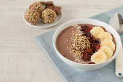 Chocolate hazelnut smoothie bowl. Topped with sliced banana, goji berries, sesame seeds and dates oatmeal energy balls royalty free stock photo