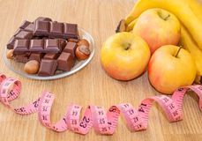 Chocolate with hazelnuts, a meter and fruits, apples, bananas, greyfruit. Chocolate or fruit diet. stock image