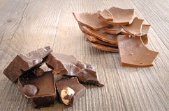 Chocolate with hazelnuts. In pieces on a rustic wooden table Stock Image