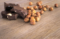 Chocolate with hazelnuts. In pieces on a rustic wooden table Royalty Free Stock Photos