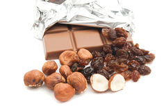 Chocolate, hazelnuts and some raisins. On white stock photo