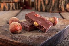 Chocolate with hazelnuts on wooden board Royalty Free Stock Images