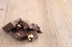 Chocolate with hazelnuts. On wooden rustico table Royalty Free Stock Photo