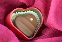 Chocolate Heart. In small tin on rink material Royalty Free Stock Images
