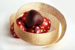Chocolate Heart. Lay at top of a hill of sweets in a red metallic paper with golden stars on white background Stock Photos
