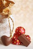 Chocolate Heart & bag for gifts. Chocolate heart lay near white & golden bag for gifts on bright background. Chocolate sweets in red metallic paper lay in the Royalty Free Stock Photo