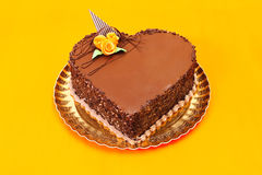 Chocolate heart cake. On orange background.  Copy space on cake Royalty Free Stock Photography
