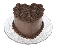 Chocolate heart cake with chocolate hand made frosting roses Iso. Chocolate heart cake with chocolate hand made frosting roses on a glass plate isolated on white Royalty Free Stock Image