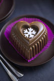 Chocolate Heart Cake with White Snowflake for New Years Eve. Cake in the purple paper Punnet on the Black Table with Christmas Tree, Candles Stock Photography