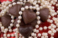 Chocolate heart candy. On a red plate with pearls Royalty Free Stock Photos