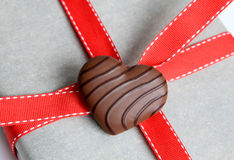 Chocolate Heart. Chocolate covered heart on a package tied with red ribbon Stock Photo