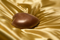 Chocolate heart on gold colored satin background. Milk chocolate heart on gold colored wrinkled smooth satin background Stock Photo