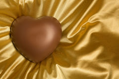 Chocolate heart on gold colored satin background. Milk chocolate heart on gold colored wrinkled smooth satin background Royalty Free Stock Photography