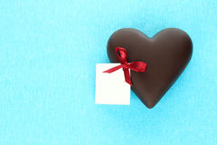 Chocolate heart with greeting card on blue background Royalty Free Stock Image