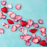 Chocolate heart and lips shaped candies with rose candied sugared petals. Blue background. Top view. stock photo