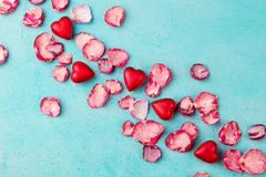 Chocolate heart and lips shaped candies with rose candied sugared petals. Blue background. Top view. stock photos