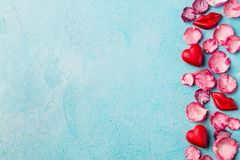 Chocolate heart and lips shaped candies with rose candied sugared petals. Blue background. Top view. Copy space. Chocolate heart and lips shaped candies with stock image