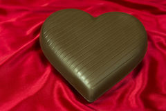 Chocolate heart on red satin Stock Image