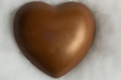 Chocolate heart resting on soft wadding. Close-up Royalty Free Stock Photos