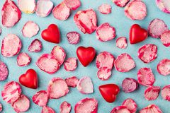Chocolate heart shaped candies with rose candied sugared petals. Blue background. Top view. royalty free stock photos
