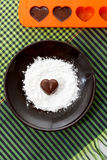 Chocolate heart-shaped candy on a brown plate with sugar powder and a bakin form with chocolates against green checked fabric back Royalty Free Stock Image