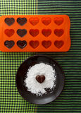 Chocolate heart-shaped candy on a brown plate with sugar powder and a bakin form with chocolates against green checked fabric back Stock Photo