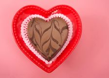 Chocolate heart shaped cheese cake on red heart shaped plate for Valentine`s Day. On pink background. Top view flat lay stock photo