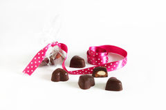 Chocolate heart shaped truffles with pink ribbon, isolated on white Royalty Free Stock Images
