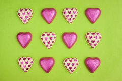 Chocolate heart shapes wrapped in tin foil. Collection of chocolate heart shapes wrapped in tin foil on green background stock images