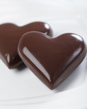 Chocolate hearts. Two chocolate hearts on white plate closeup Royalty Free Stock Photography