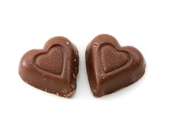 Chocolate hearts. Two chocolate hearts on a white background royalty free stock photos