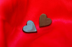 Chocolate hearts. Two heart-shaped chocolates on red satin background. Be my Valentine Royalty Free Stock Photos