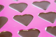Chocolate in Hearts. Close up of warm chocolate that has just been poured into a heart mold Stock Images